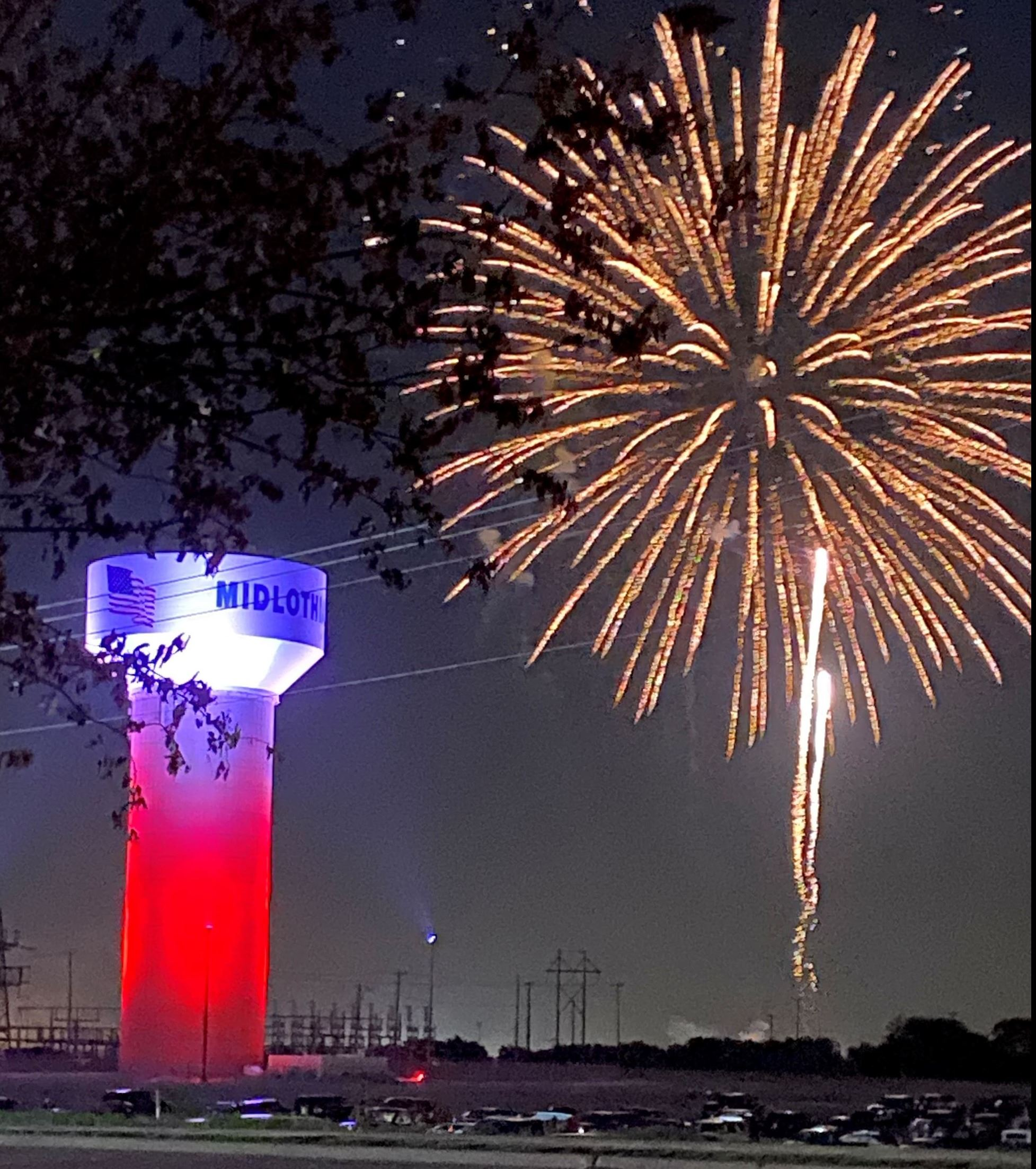 Water tower with red/blue lights and a large gold firework in the sky.
