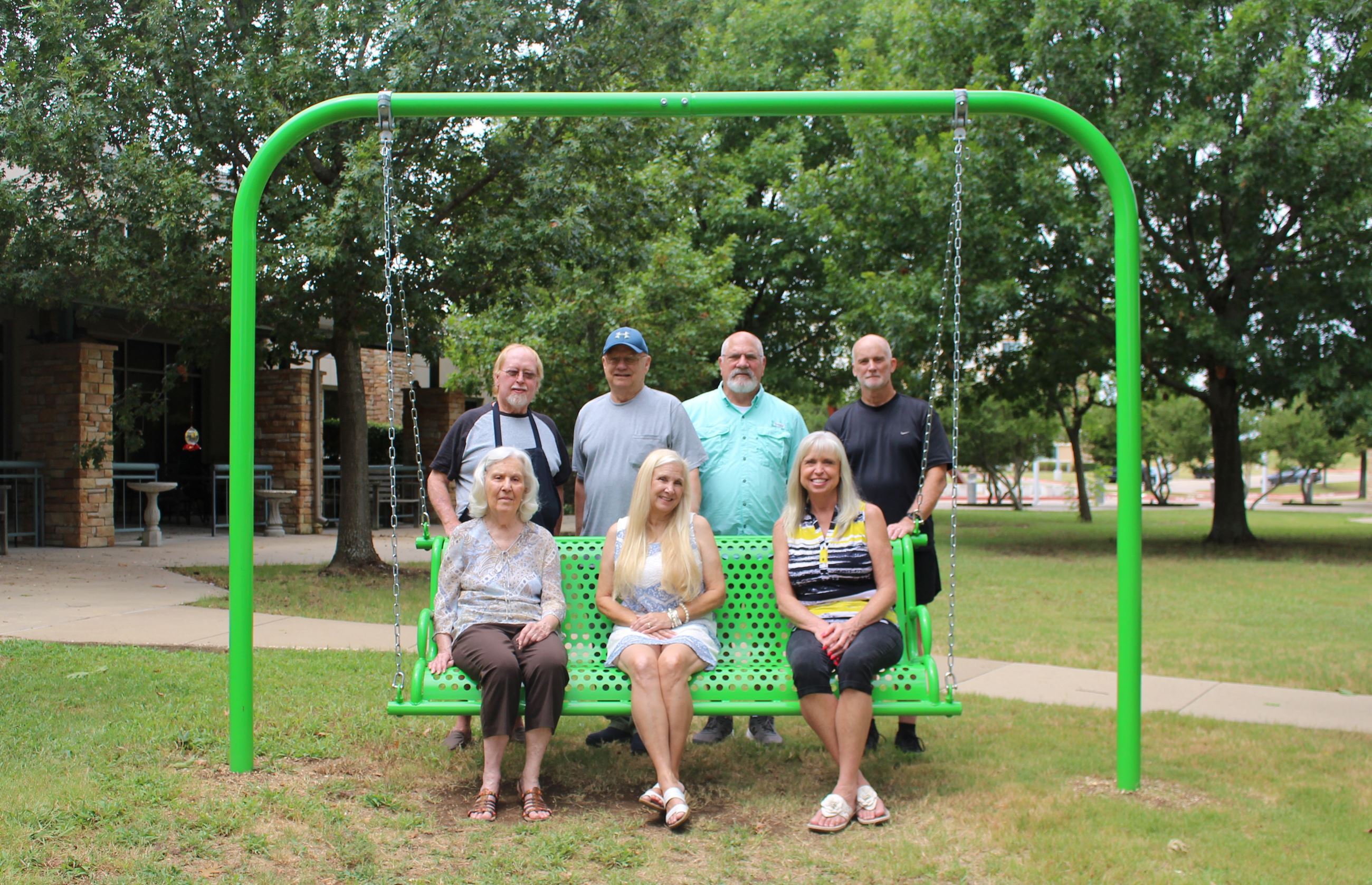 photo of a green swing with seven staff members